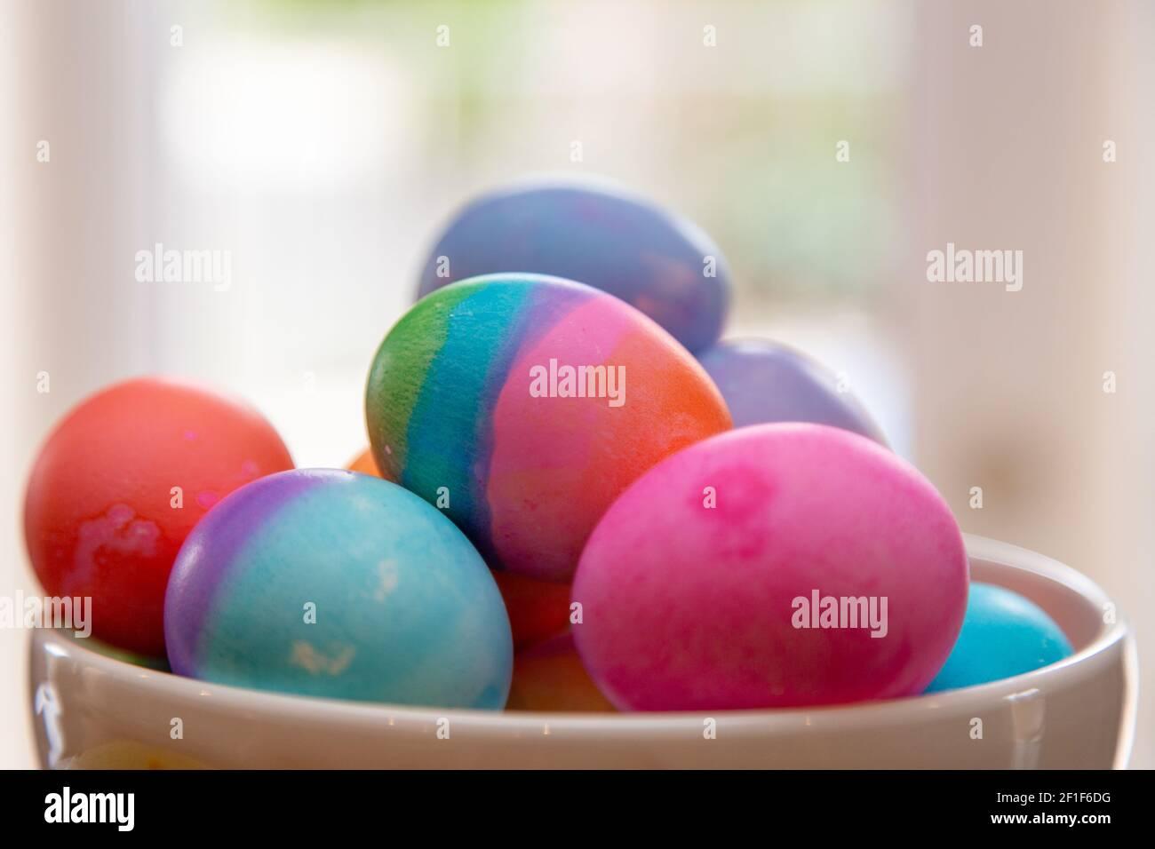 Primer plato de huevos de Pascua de colores brillantes en juego Foto de stock