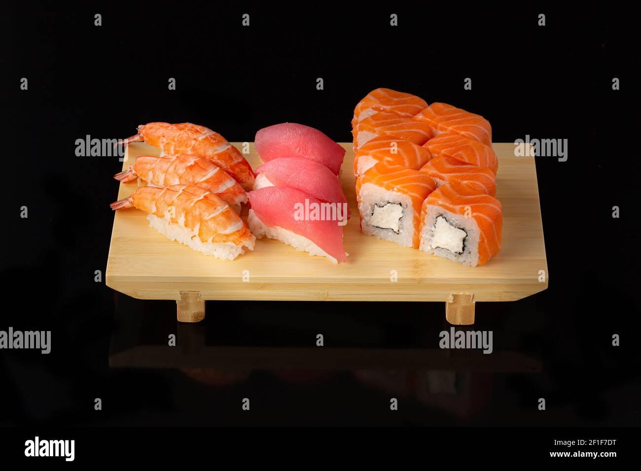 Set de sushi. Rollos con caviar rojo de anguila de salmón y verduras sobre fondo negro. Foto de stock