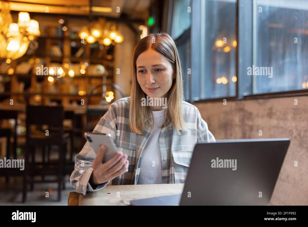 Joven mujer de negocios caucásica con cabello rubio trabajando en el portátil en el café. Estudiante universitario usando tecnología, educación en línea, independiente Foto de stock