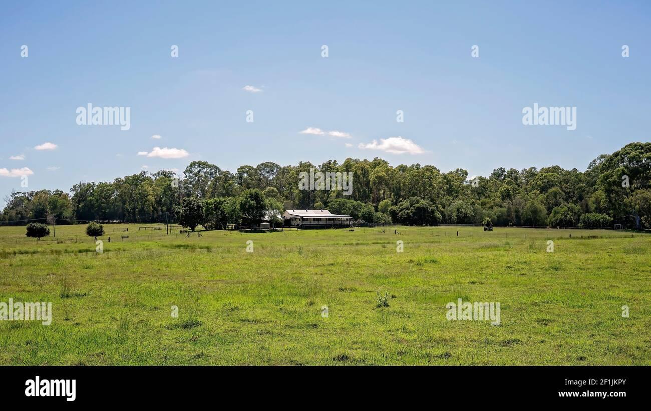 Una hacienda rural en hectáreas de campos verdes Foto de stock