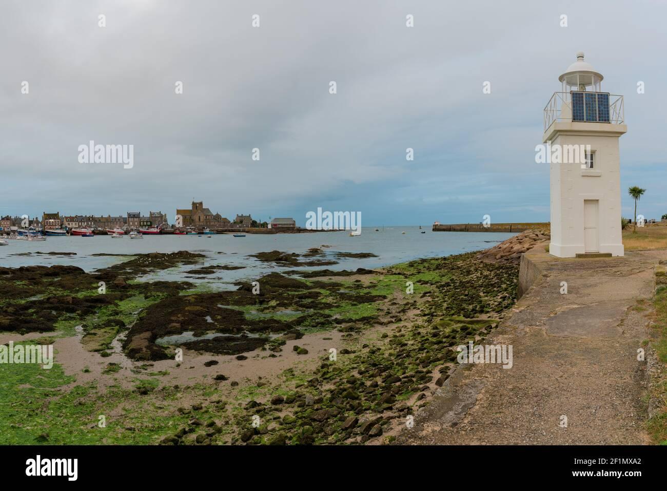 El faro del puerto de Barfleur y el puerto en la marea baja la noche Foto de stock