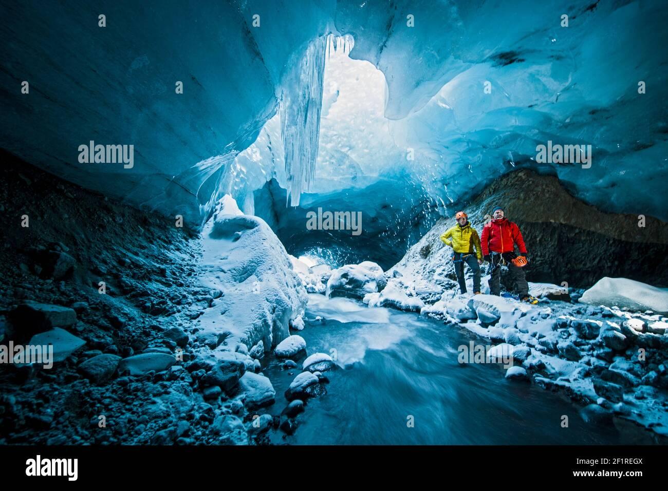 Hombres explorando la cueva de hielo en Thórsmörk - Islandia Foto de stock