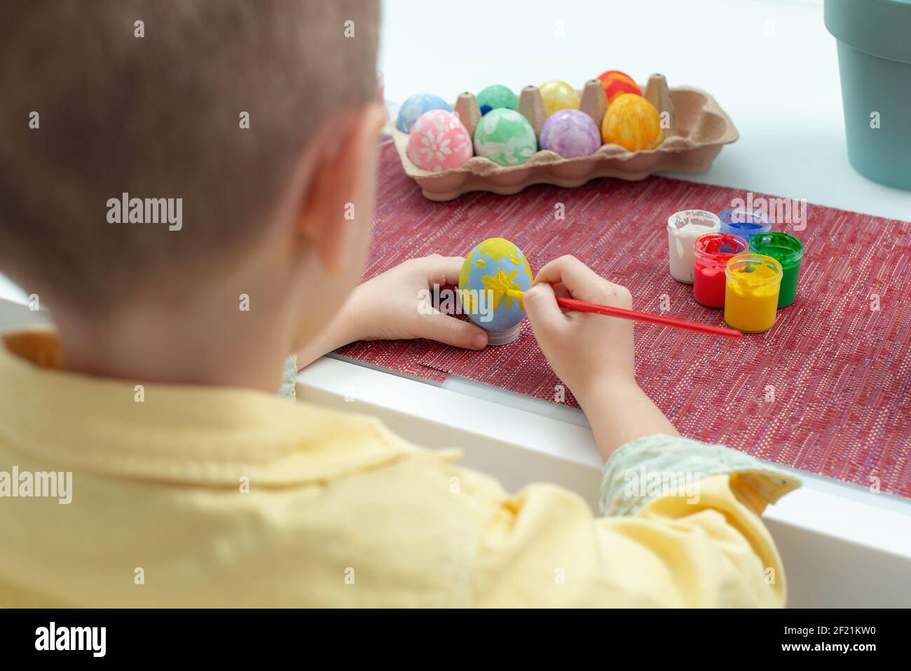 Creadora Caucásica niño pintando huevos de Pascua. Niño preescolar decorar y pintar huevos de pascua en diferentes colores. Preparación para la fiesta EAS Foto de stock
