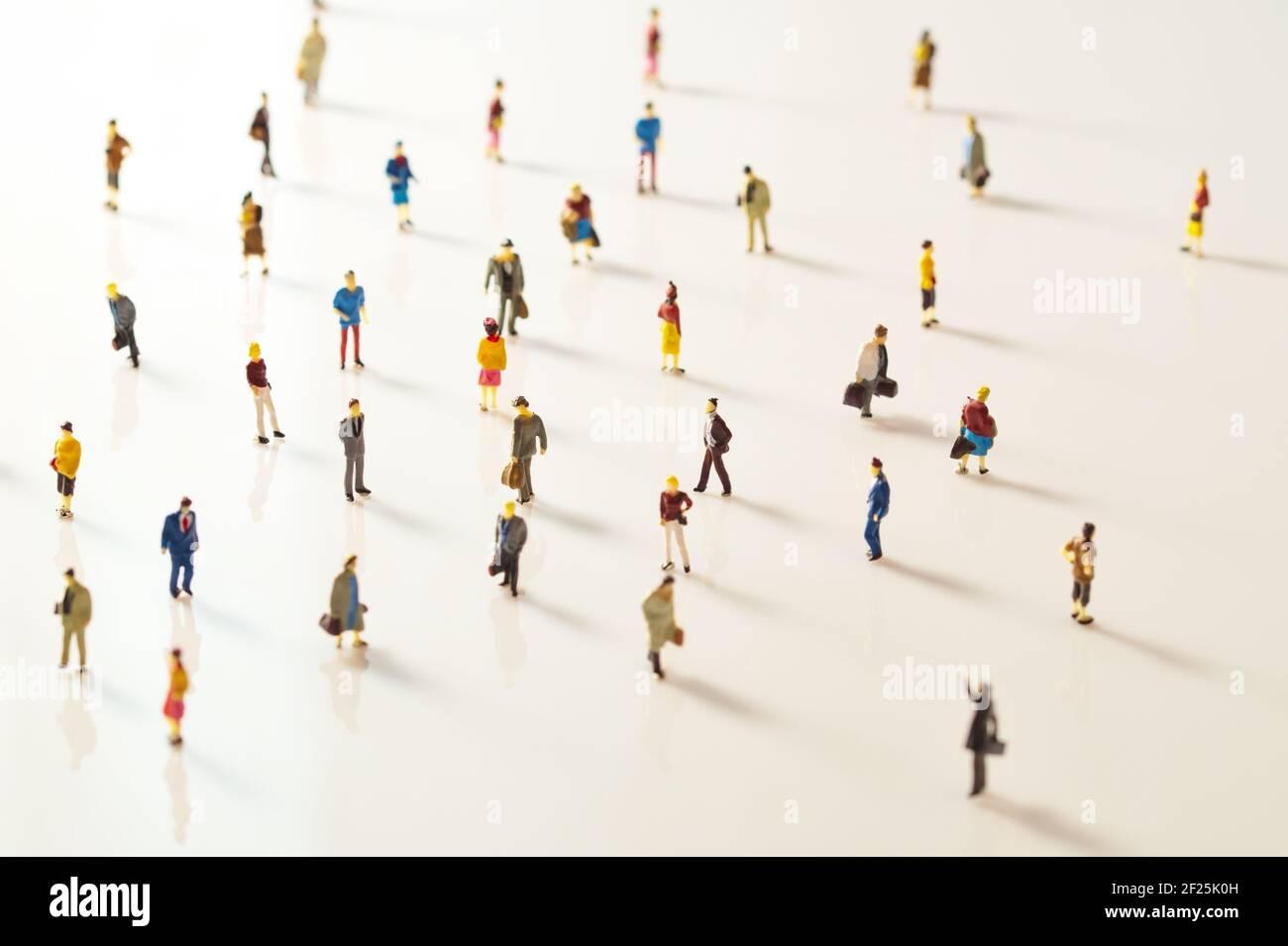 Gente de juguete, figurillas en miniatura manteniendo la distancia en público. Distanciamiento social debido al Covid-19 Foto de stock