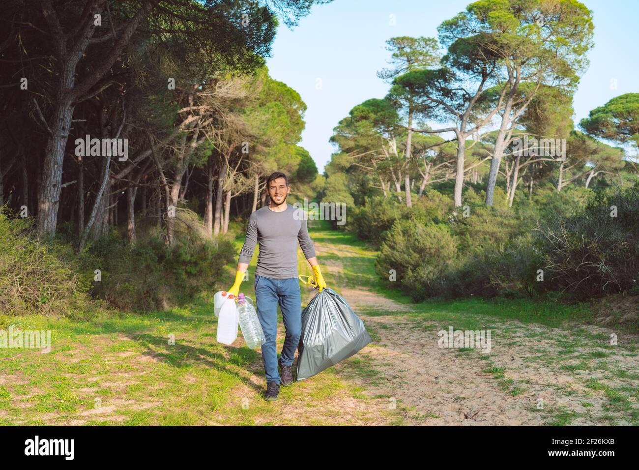 Hombre voluntario con bolsa de basura limpiando el bosque de plástico contaminación Foto de stock