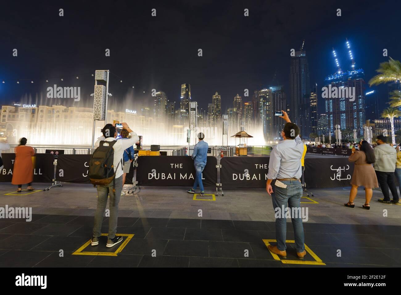 El espectáculo de la Fuente de Dubai con marcas de terreno para el distanciamiento social para los turistas que viajan durante la pandemia. Atracción turística durante COVID-19 en Dubai. Foto de stock