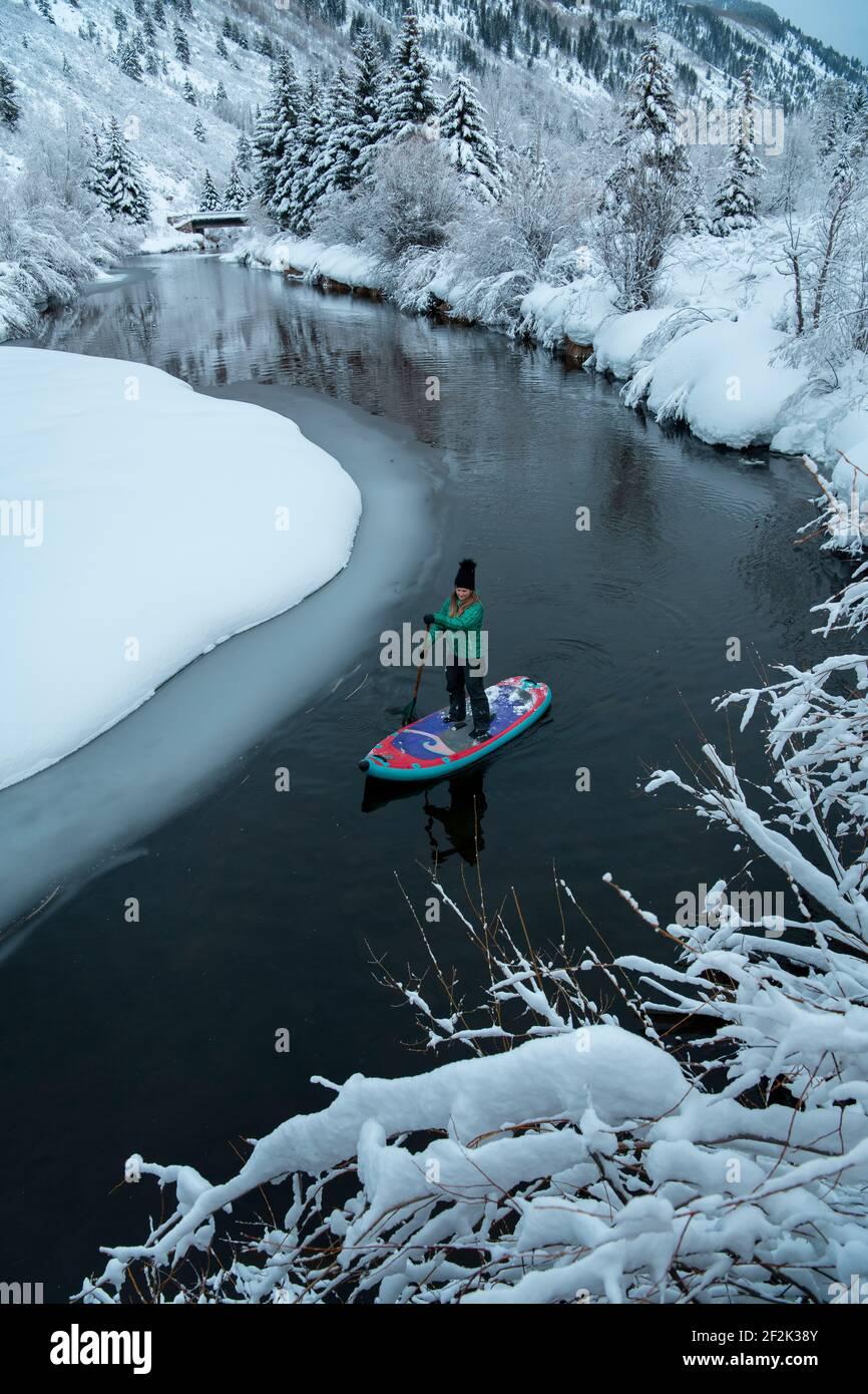 Mujer paddleboarding en el río durante el invierno Foto de stock