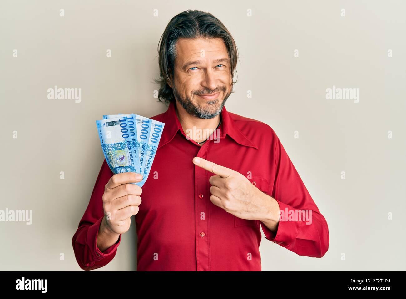 Hombre guapo de mediana edad con 1000 billetes de forint húngaros sonriendo feliz señalar con la mano y el dedo Foto de stock