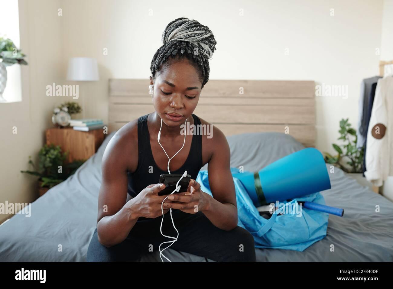 Mujer negra bastante adecuada sentada en la cama y eligiendo música para entrenar en su smartphone Foto de stock