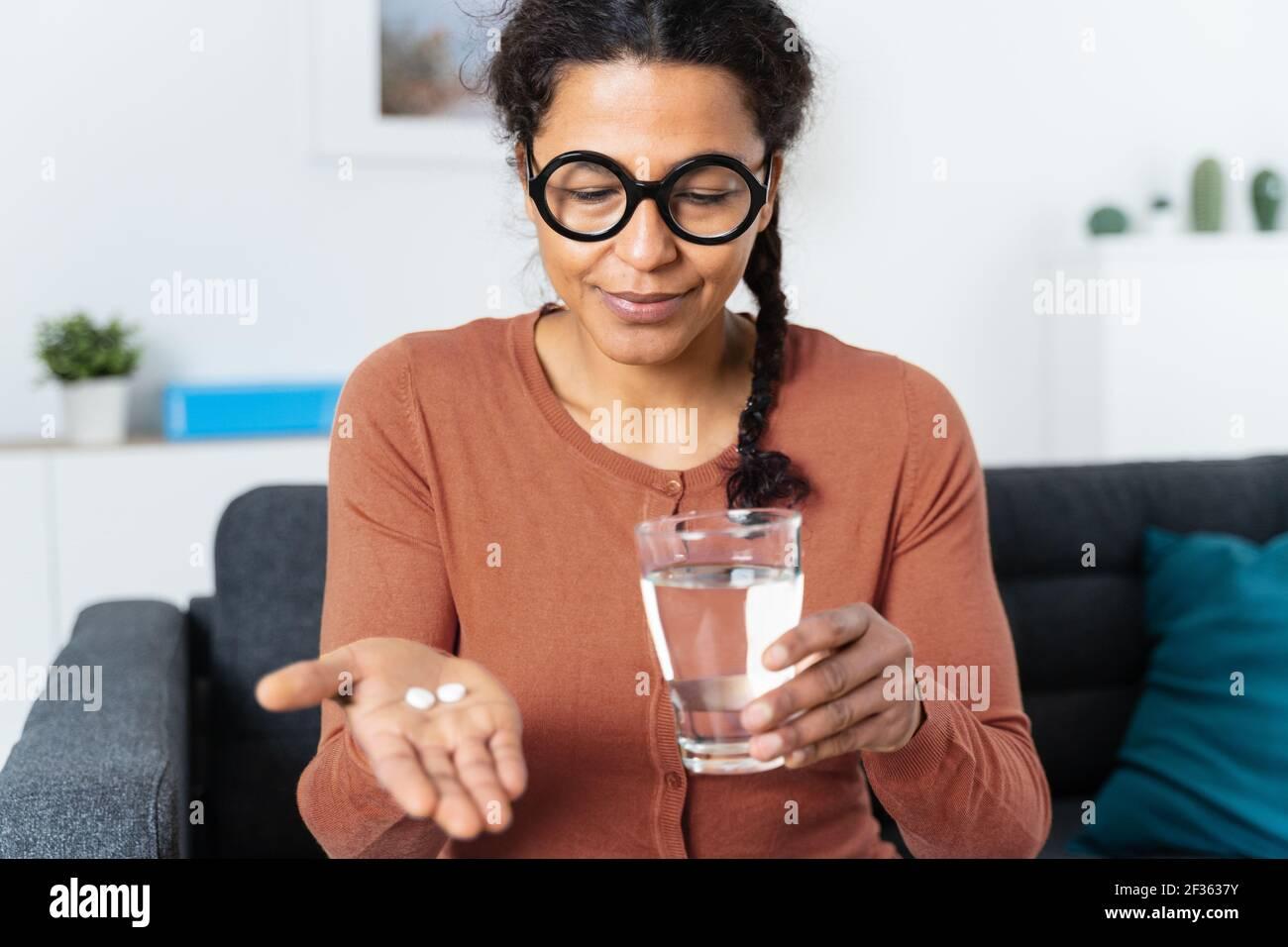 Mujer afroamericana que sostiene píldoras de medicina en la mano Foto de stock