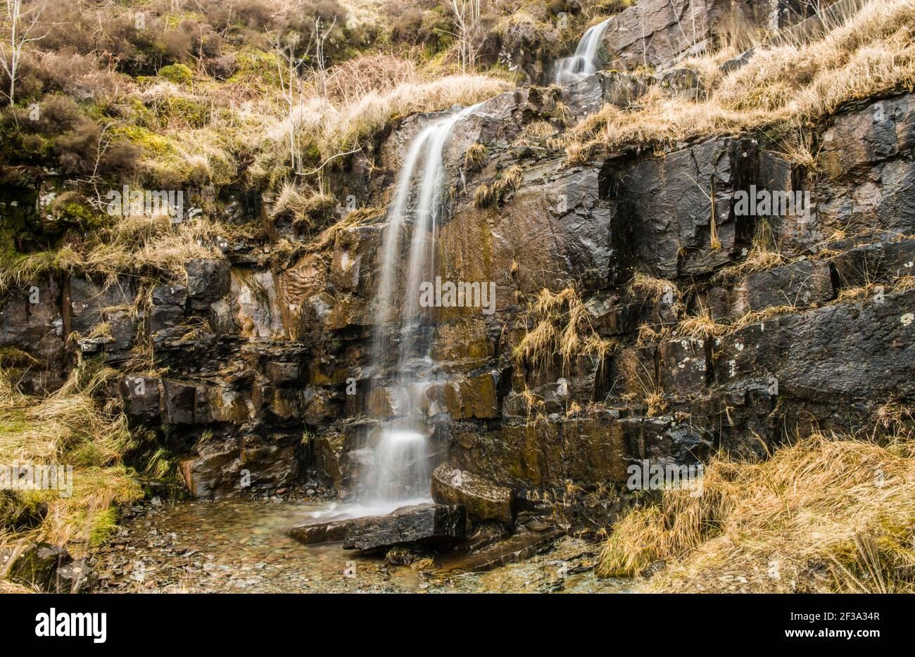 Una cascada en el lado del A470 sobre el Parque Nacional Brecon Beacons Foto de stock