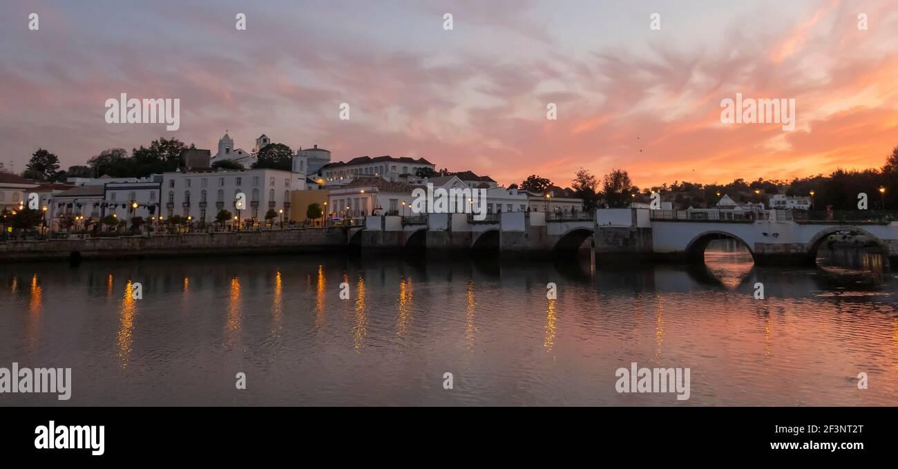 Puesta de sol sobre el puente romano a través del río Gilao en Tavira, Algarve Oriental, Portugal Foto de stock