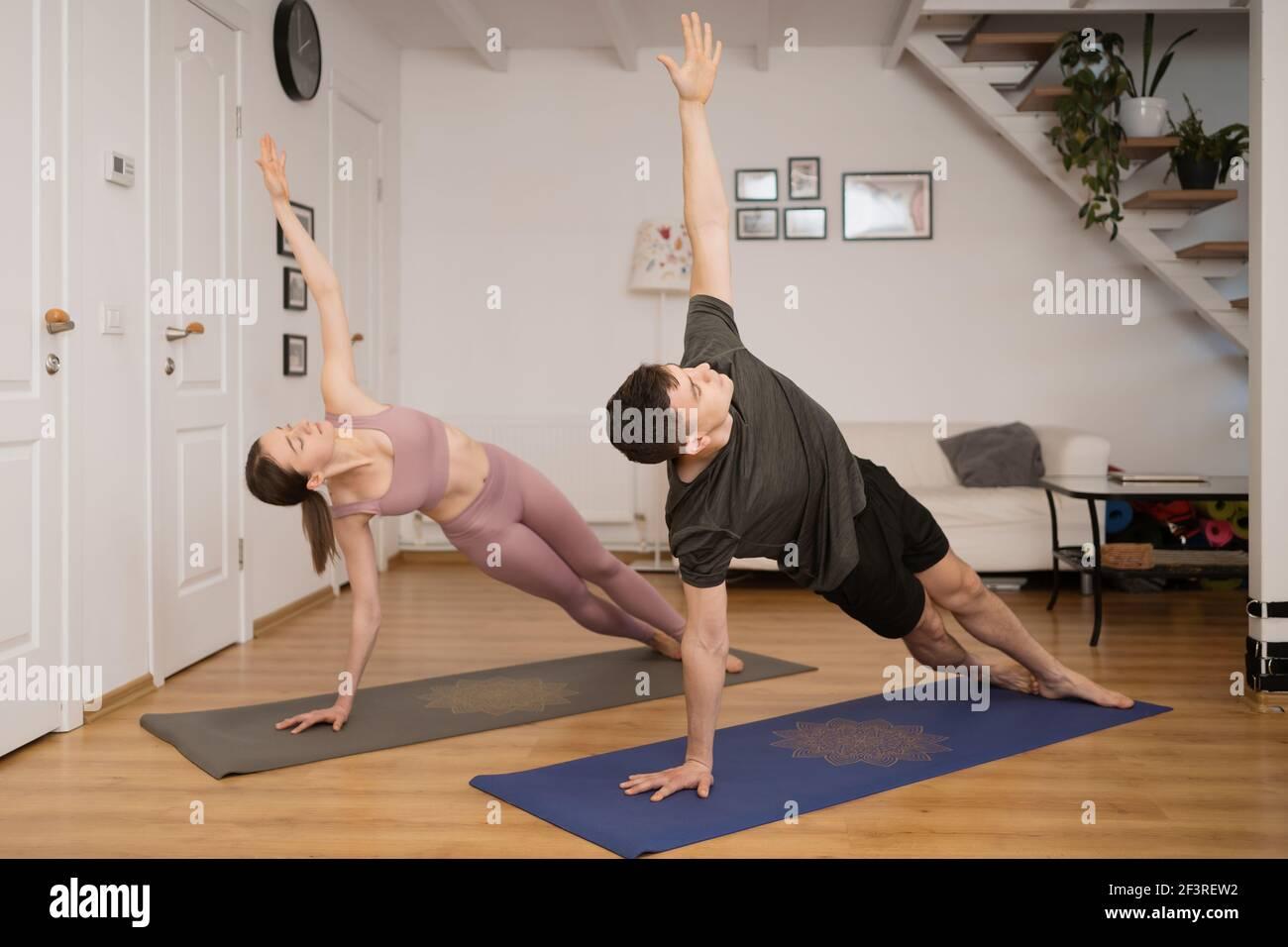 Pareja joven practicando yoga juntos en casa en un interior moderno. Afición, unión, estilo de vida saludable Foto de stock