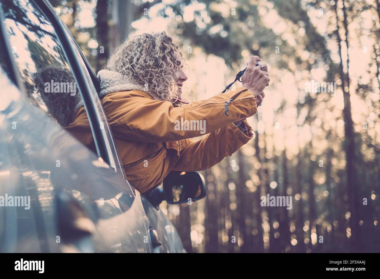 vacaciones de aventura, vacaciones, viajes, viaje por carretera y concepto de la gente - feliz y sonriente joven mujer adulta o joven fuera de la ventana del coche tomando pict Foto de stock