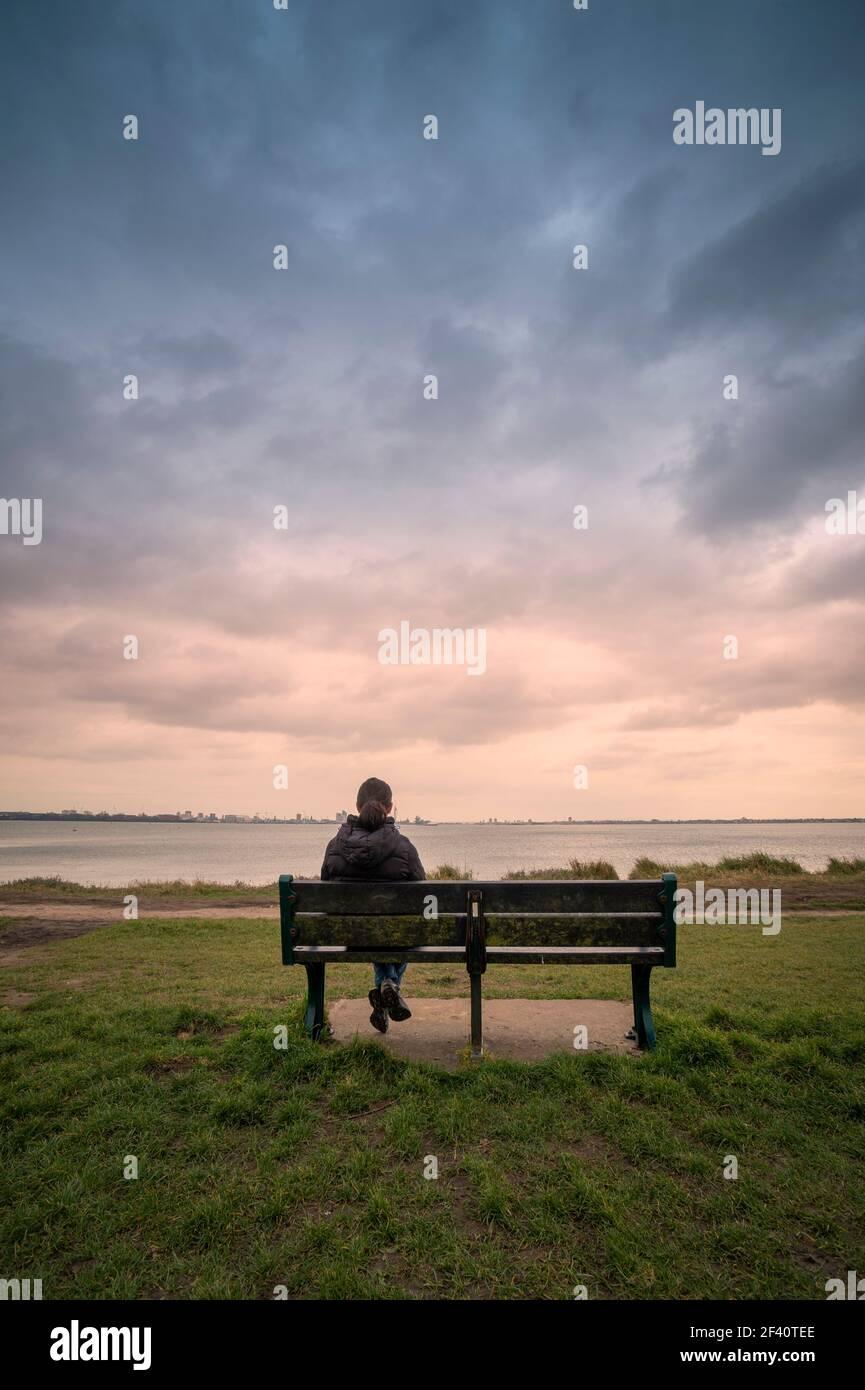Vista posterior de una mujer sentada en un banco, mirando al mar, cielo estrellado. Foto de stock
