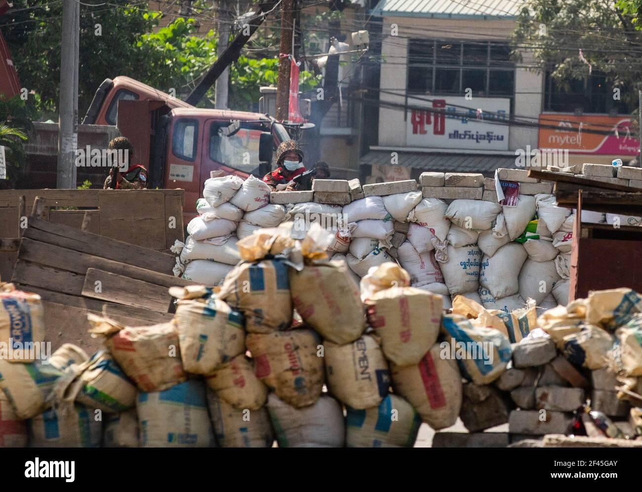 Los soldados militares de Myanmar (Tatmadow) sonreían mientras apuntaban rifles hacia los manifestantes contra el golpe militar durante una manifestación contra el golpe militar. La policía y los soldados militares de Myanmar (tatmadow) atacaron a los manifestantes con balas de goma, municiones vivas, gases lacrimógenos y bombas de aturdimiento en respuesta a los manifestantes contra el golpe militar el viernes, matando a varios manifestantes e hirieron a muchos otros. Al menos 149 personas han sido asesinadas en Myanmar desde el golpe de Estado del 1 de febrero, dijo un funcionario de derechos humanos de la ONU. Los militares de Myanmar detuvieron a la Consejera de Estado de Myanmar Aung San Suu Kyi el 01 de febrero de 2021 y de Foto de stock