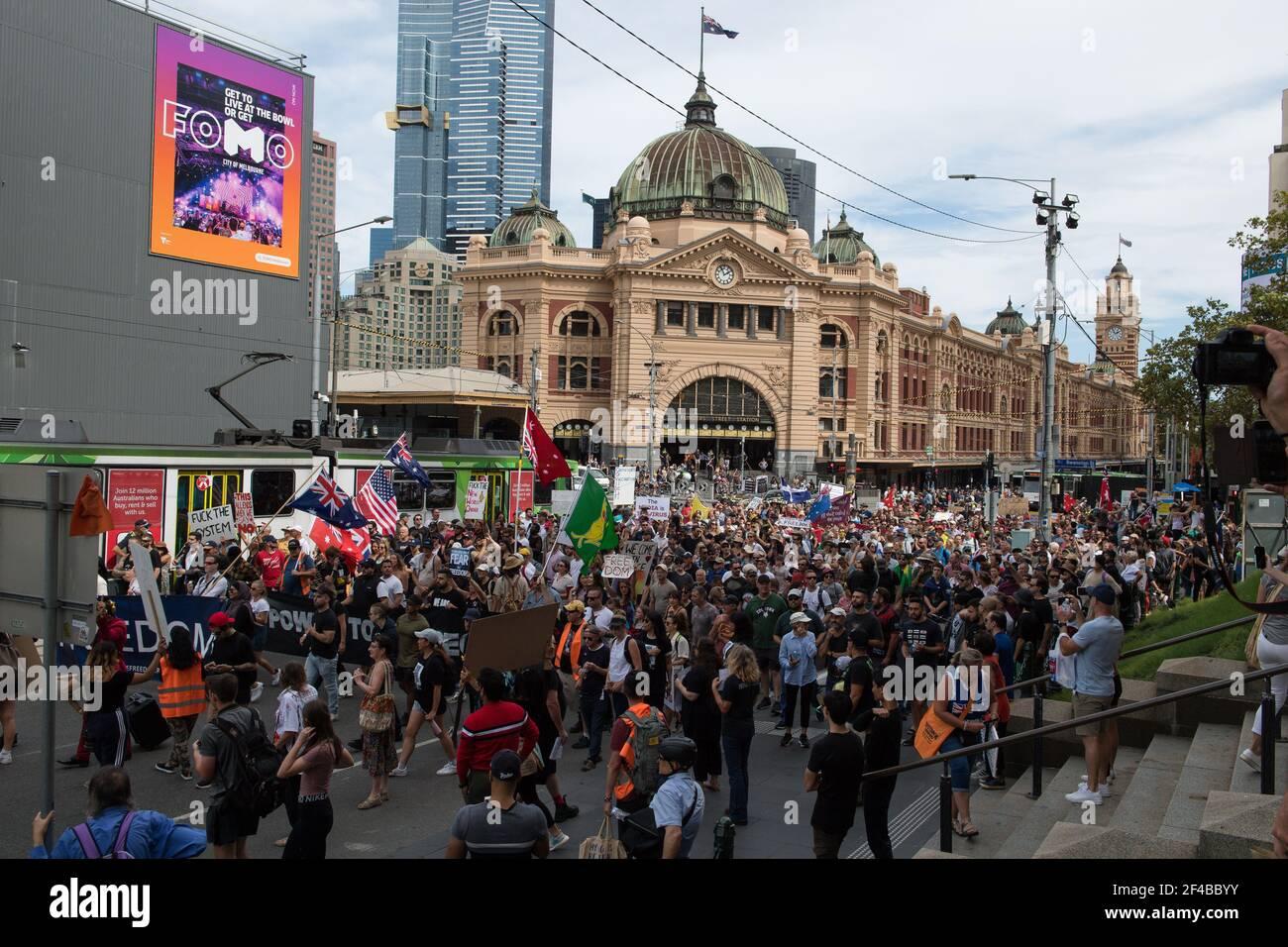 """Melbourne, Australia 20 de marzo de 2021, los manifestantes pasan por la estación de Flinders Stree mientras salen a las calles en el Freedom Rally que fue parte de una demostración del planeado """"World Wide Rally for Freedom"""" que fue organizado para llamar a la libertad de elección, el discurso y el movimiento. Crédito: Michael Currie/Alamy Live News Foto de stock"""