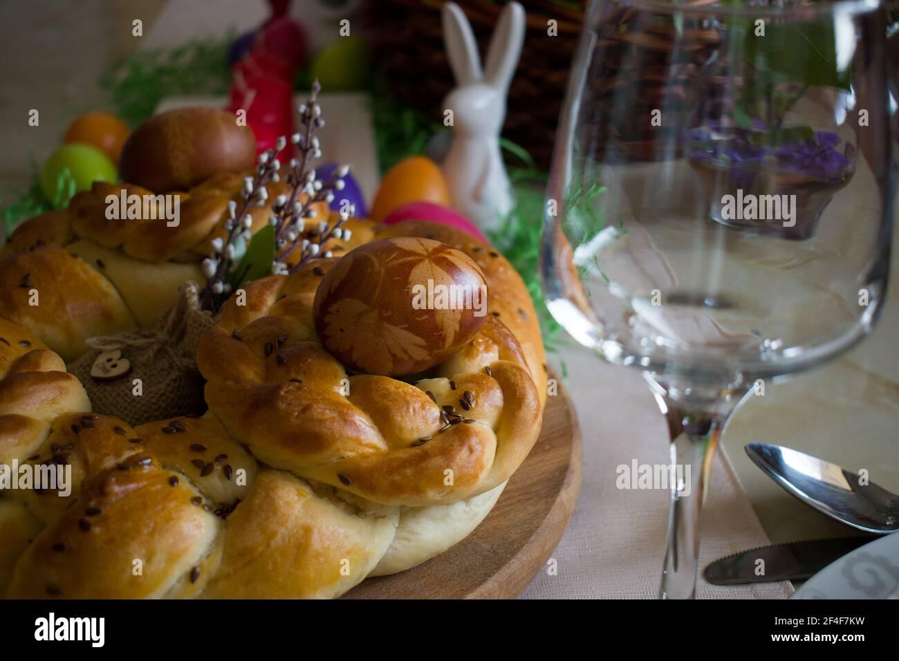 Primer plano de la decoración de la mesa de Pascua. Tradicional pan trenzado casero y huevos teñidos naturales con pieles de cebolla Foto de stock
