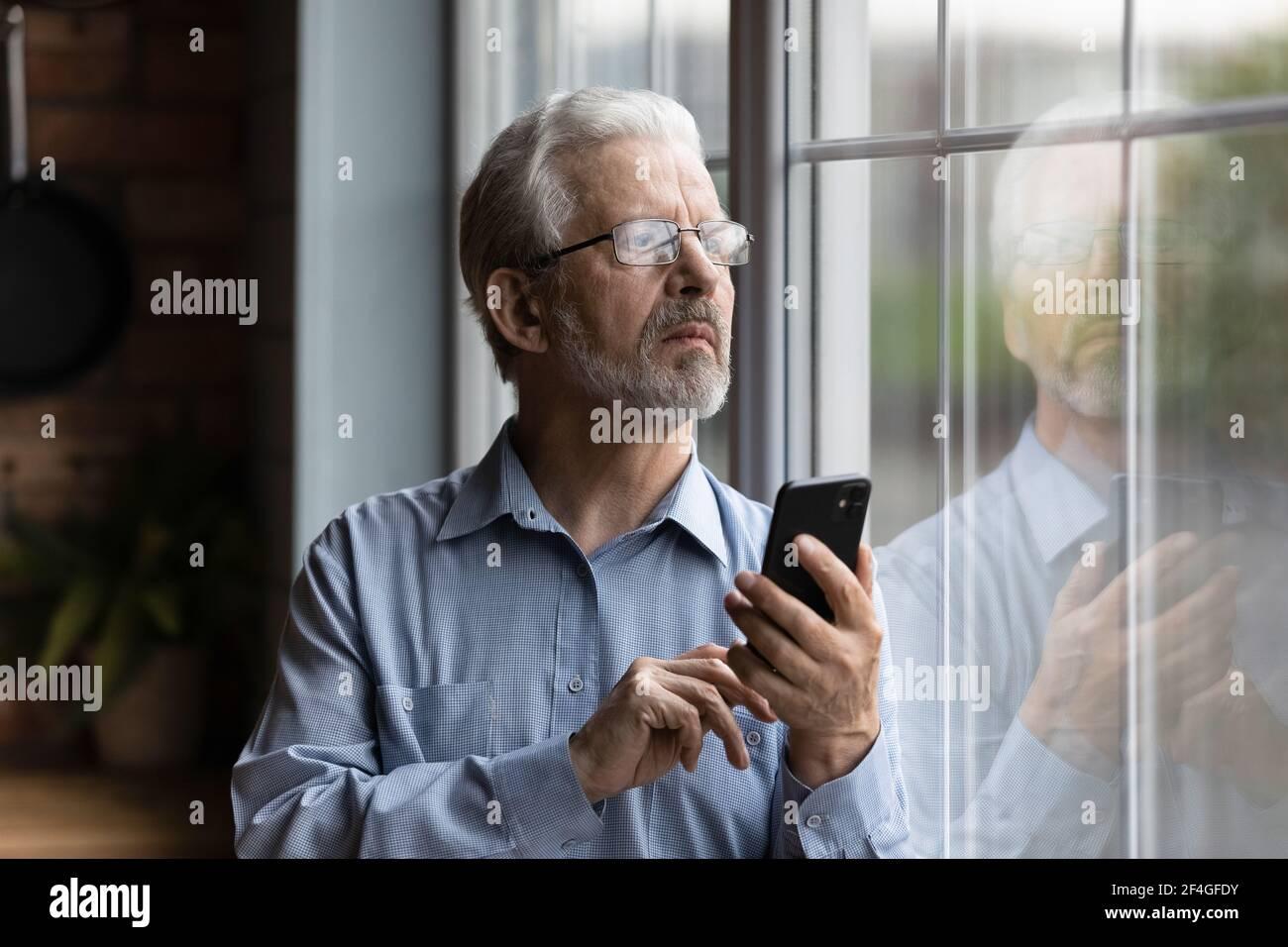 Un hombre mayor preocupado mira a la ventana de espera teléfono hacer llamada Foto de stock