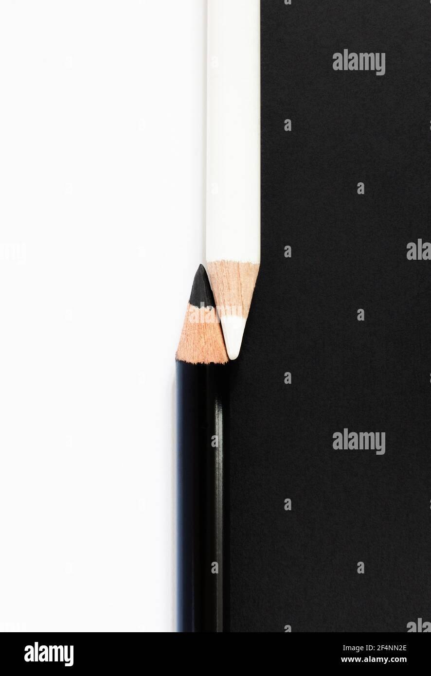 Lápices blancos y negros contra fondo contrastante para ilustrar la raza Concepto de diversidad Foto de stock