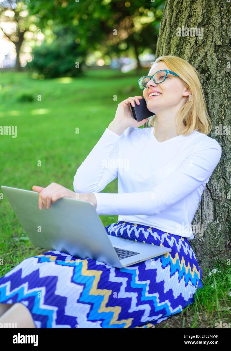 Niña sentada hierba con cuaderno. Mujer con ordenador portátil en el parque orden artículo en el teléfono. Chica se aprovecha de las compras en línea. Ahorre tiempo con las compras Foto de stock