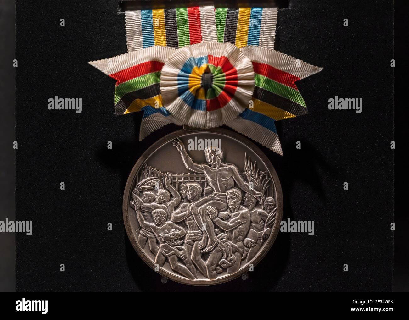 tokio, japón - marzo 2 2021: Primer plano de la medalla de plata oficial de gimnasia utilizada durante los Juegos Olímpicos de Verano de Tokio de 1964 exhibida en el Oly de Japón Foto de stock