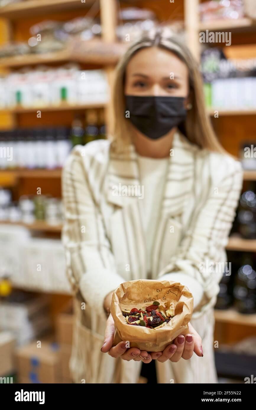 Mujer mostrando comida orgánica en bolsa de papel en la tienda Foto de stock