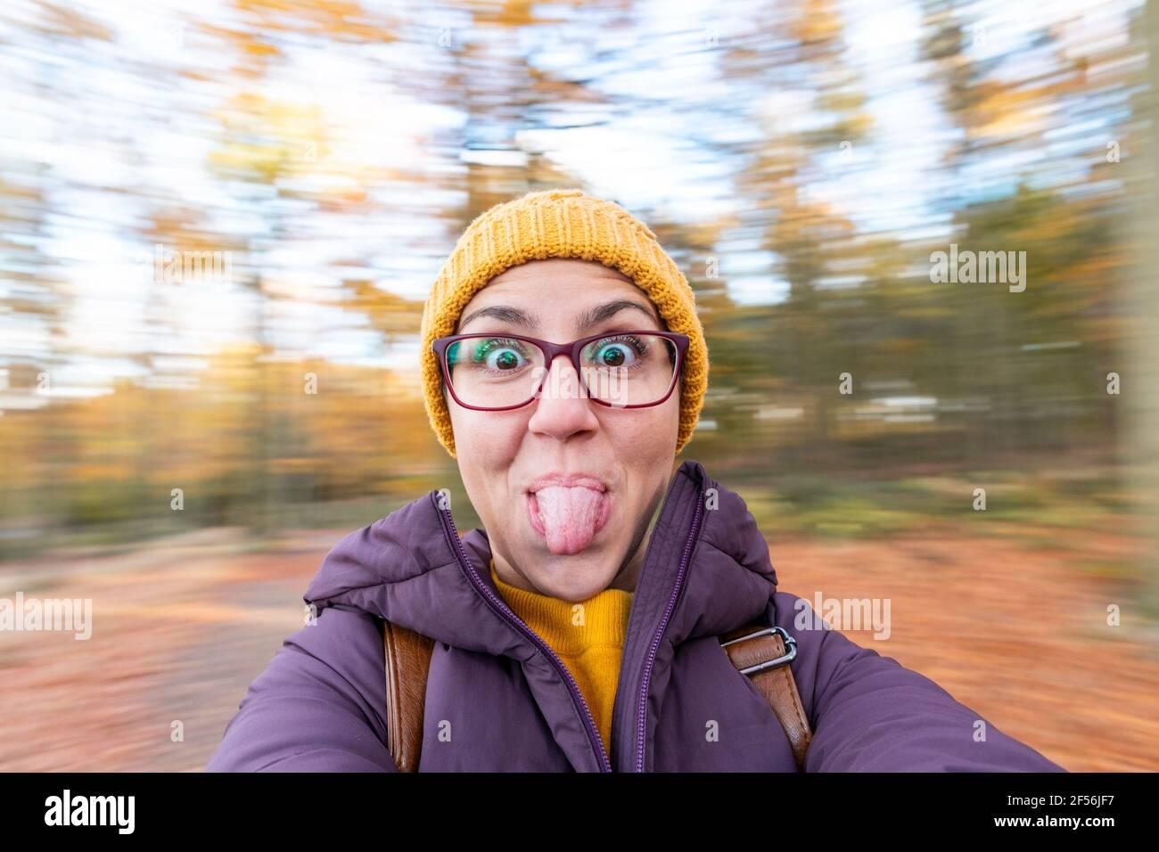 Mujer despreocupada que sobresale la lengua contra el fondo borroso en el bosque Foto de stock