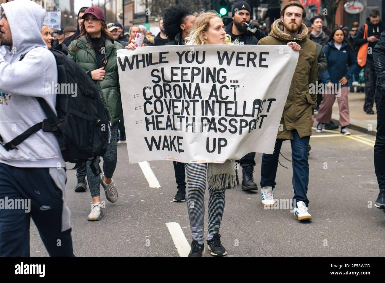 Londres, Reino Unido, 20th de marzo de 2021. Alrededor de 6000 manifestantes contra el bloqueo y la vacunación y contra la Policía, el crimen, la sentencia y los tribunales Bill march en el centro de Londres. La protesta comenzó en Hyde Park con una serie de detenciones y un discurso de Piers Corbyn, que se presenta a la alcaldía de Londres, marchó sin problemas por el centro de Londres y terminó con un puesto de atrás en Hyde Park entre unos 200 manifestantes y la policía antidisturbios restantes. Una mujer tiene una bandera que insta a la gente a despertar a los gobiernos la introducción del proyecto de ley Covid y los pasaportes de salud Foto de stock