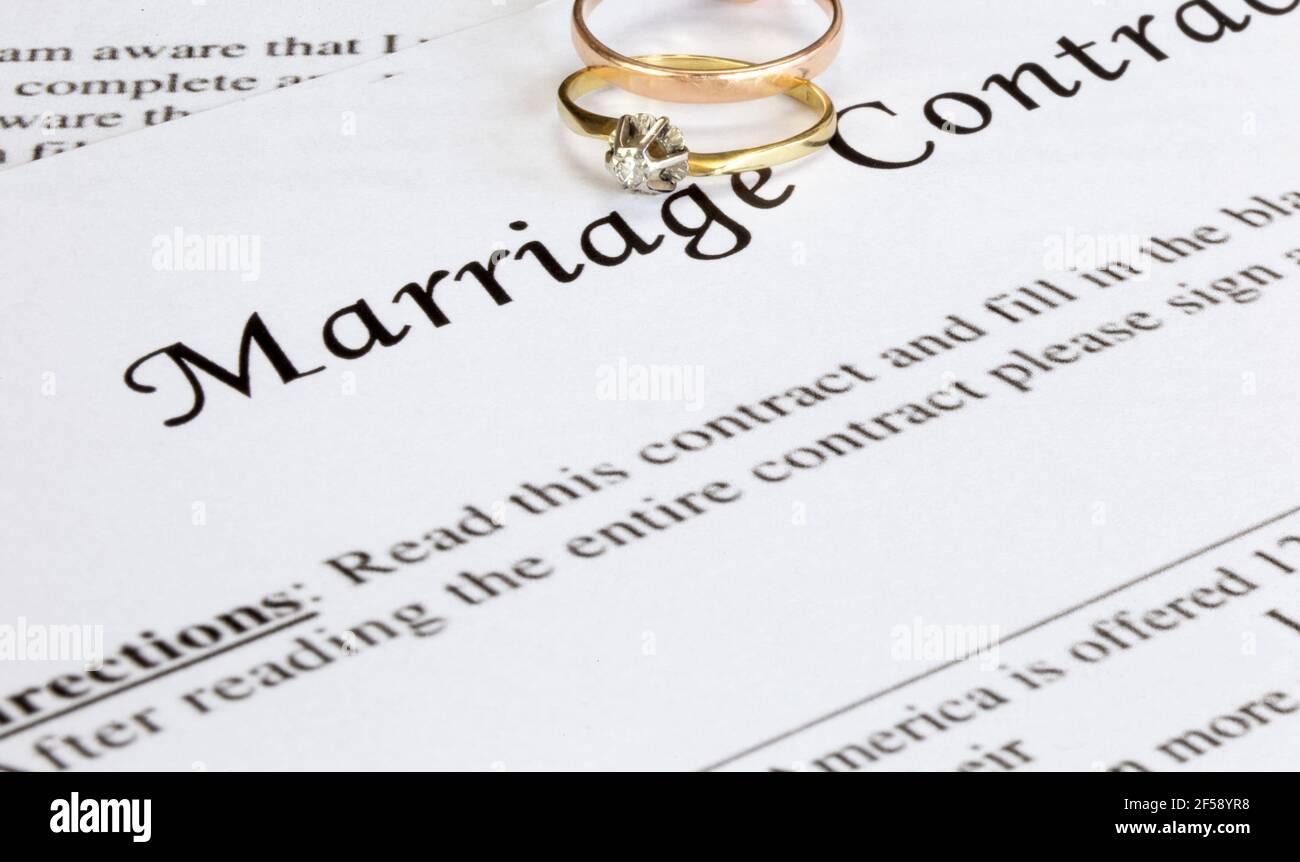 Contrato de matrimonio con dos anillos de boda de oro y pluma de oro, prenuptial acuerdo, macro primer plano, signo con firma, documento, concepto de acuerdo Foto de stock