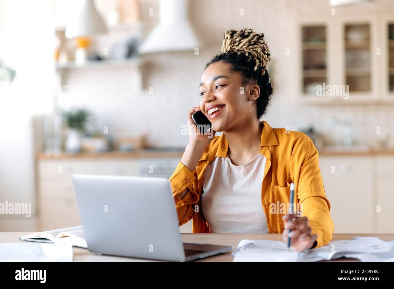 Afroamericano alegre atractiva joven con estilo, independiente, gerente o agente inmobiliario, tener una agradable conversación telefónica con el cliente o empleado, sentarse en el lugar de trabajo, sonriendo Foto de stock