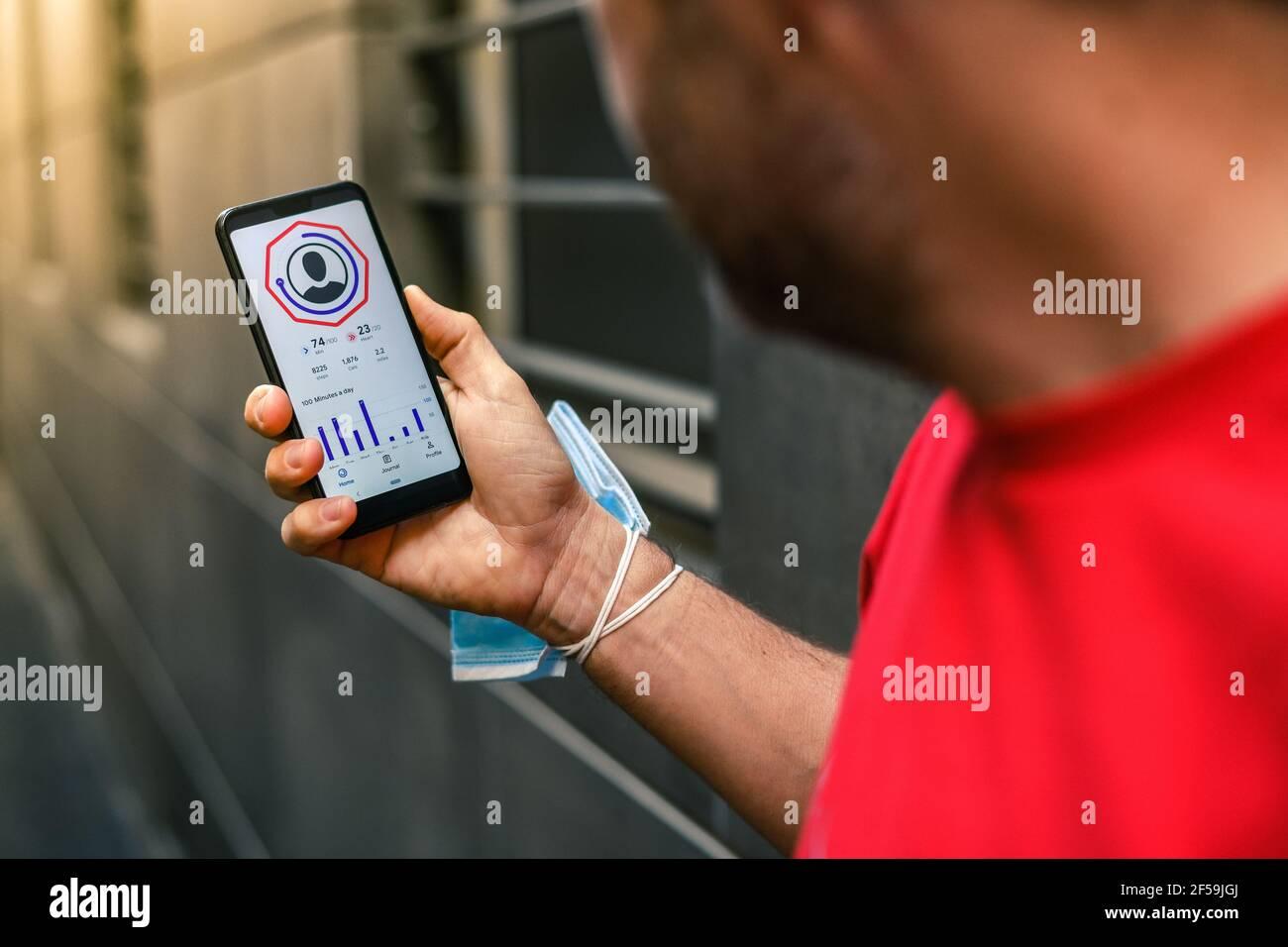 Primer plano de manos masculinas con la aplicación de ejercicio en el smartphone. Hombre descansando después de correr leyendo resultados de carrera. Hombre corriendo con teléfono móvil conectado a un sm Foto de stock