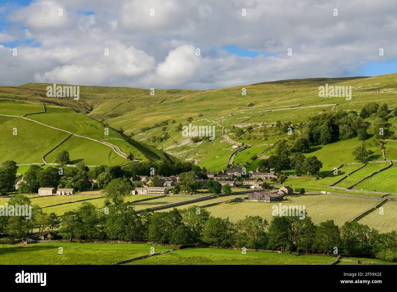 Pintoresco pueblo de Dales (casas de piedra) situado en el valle iluminado por el sol por campos, colinas, laderas y garganta empinada - Starbotton, Yorkshire Inglaterra Reino Unido. Foto de stock