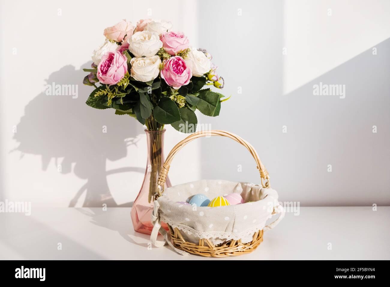 Huevos coloridos de Pascua en buket sobre mesa de madera blanca. Ramo de flores de rosas en el fondo. Felices Pascuas. Estado de ánimo de primavera. Foto de stock