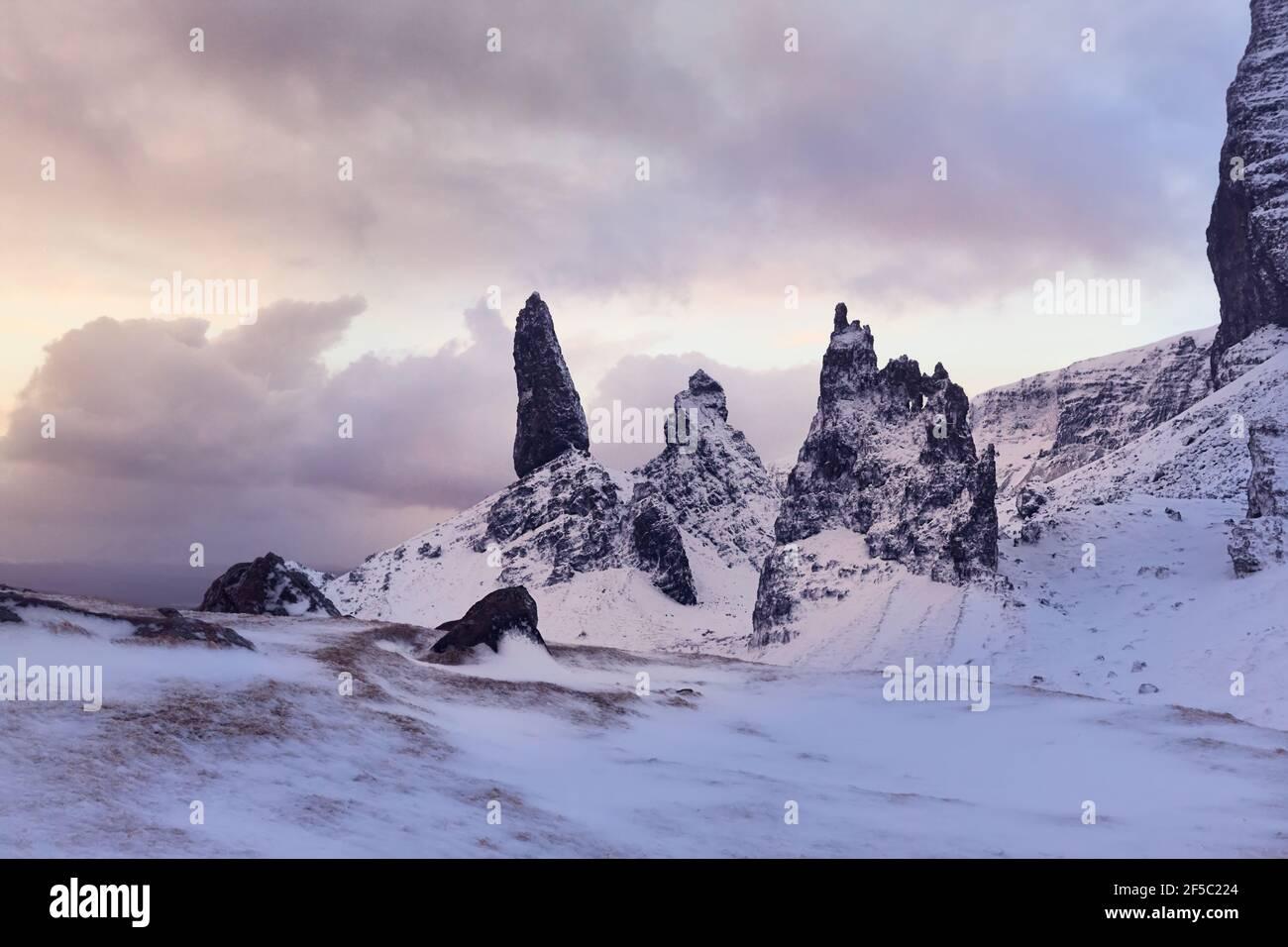 Old Man Storr, Isle Skye, Escocia. Invierno, montaña muy nevada en un amanecer muy potente. La primera mañana se ilumina entre las nubes Foto de stock