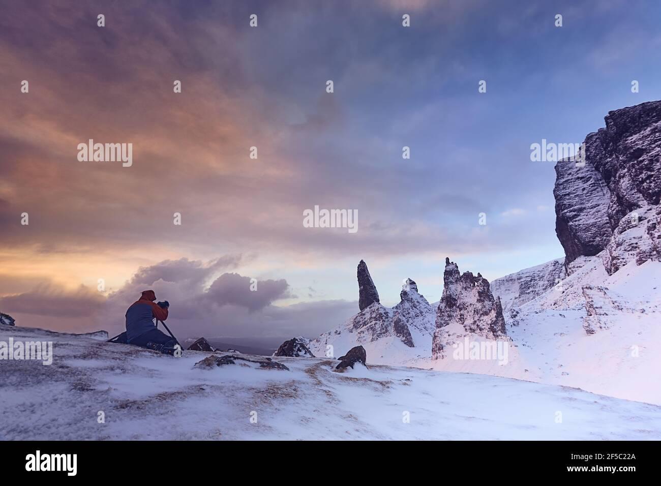 Fotógrafo fotografiado de Old Man Storr, Isle Skye, Escocia. Invierno, montaña muy nevada en un amanecer muy potente Foto de stock