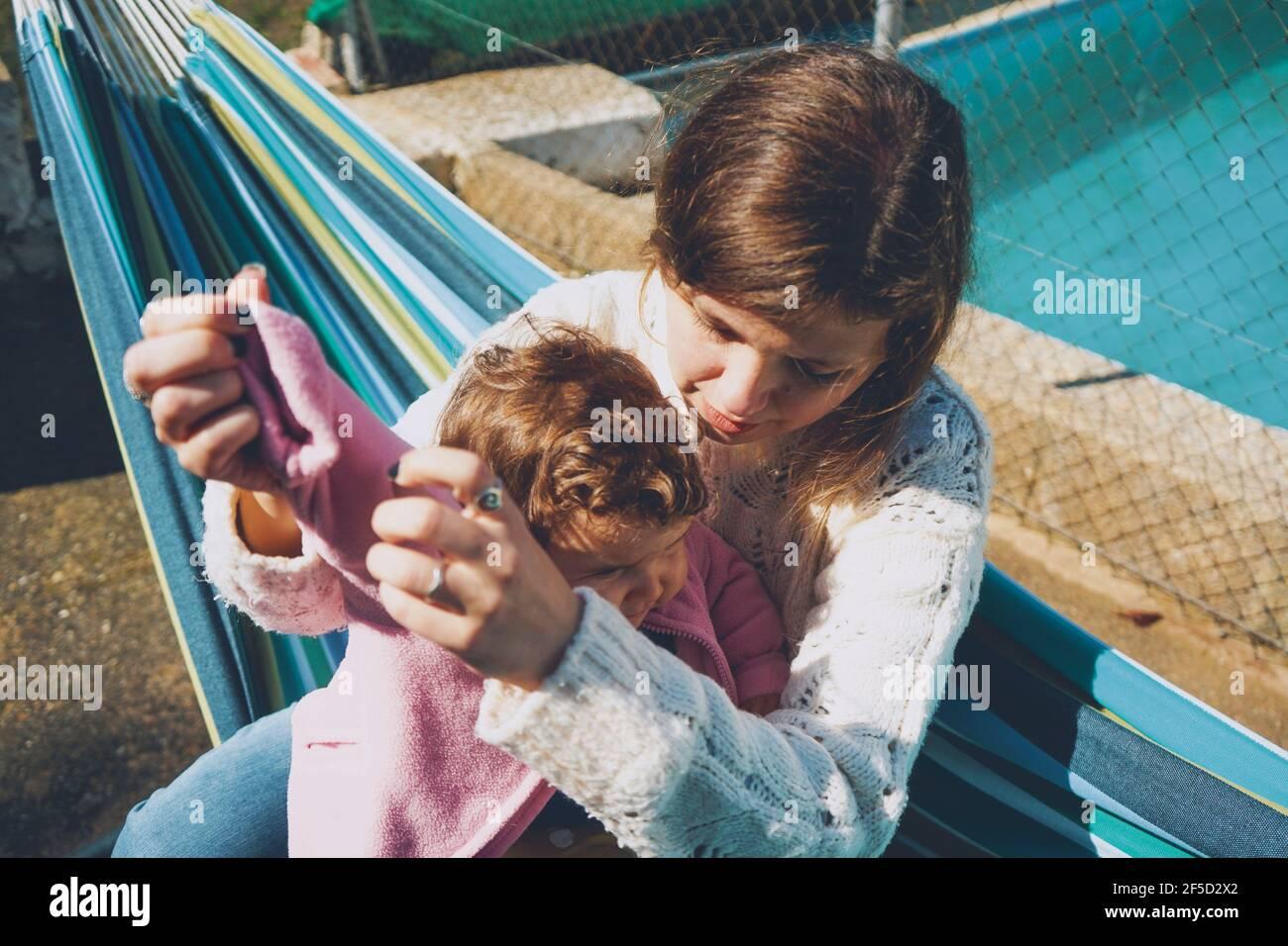 Mujer joven cuidando a su bebé sentado en una hamaca Foto de stock