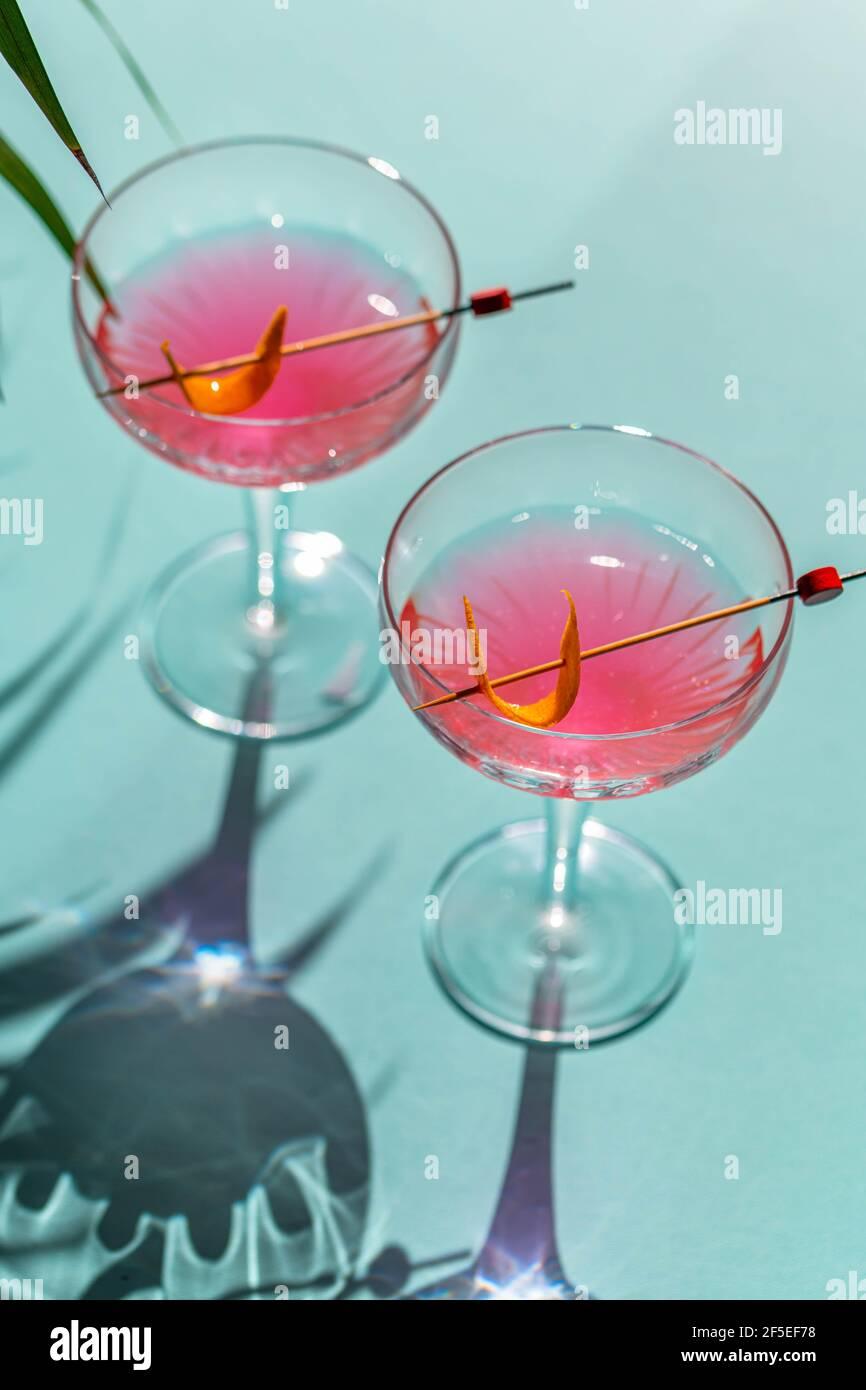 Un cóctel en un vaso con pimiento rojo frío y una tabla de cortar con pimienta, ingredientes de jengibre en el fondo. Foto de stock