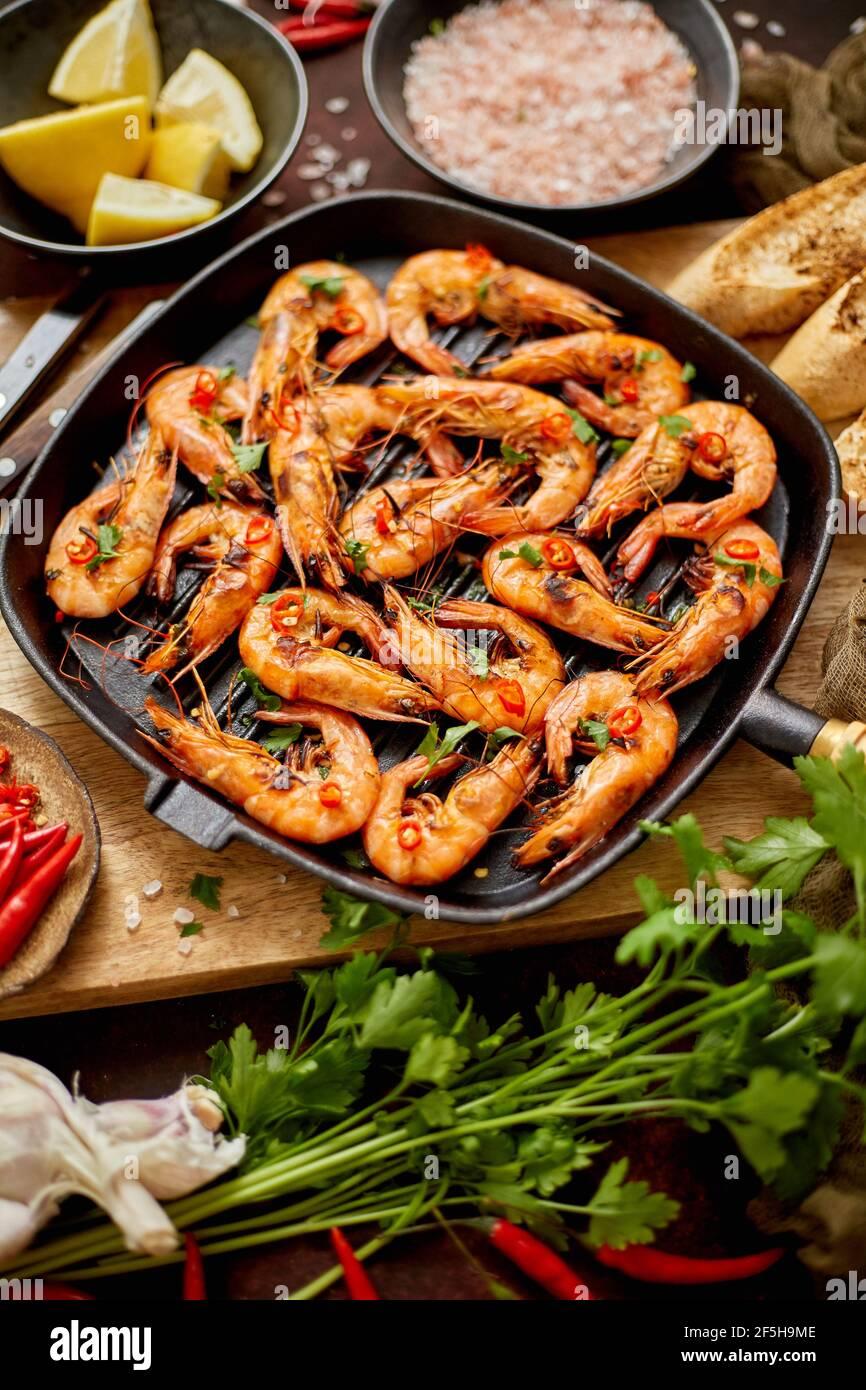 Gambas de tigre asadas en una sartén de hierro con pernera fresca, limón, Chile y pan Foto de stock