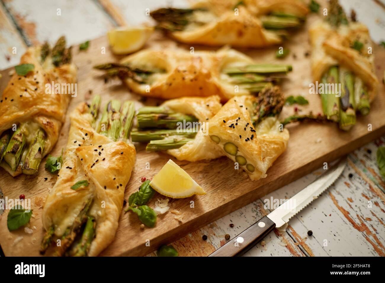 Espárragos verdes horneados envueltos en hojaldre. Servido en tabla de madera. Con enfoque selectivo Foto de stock