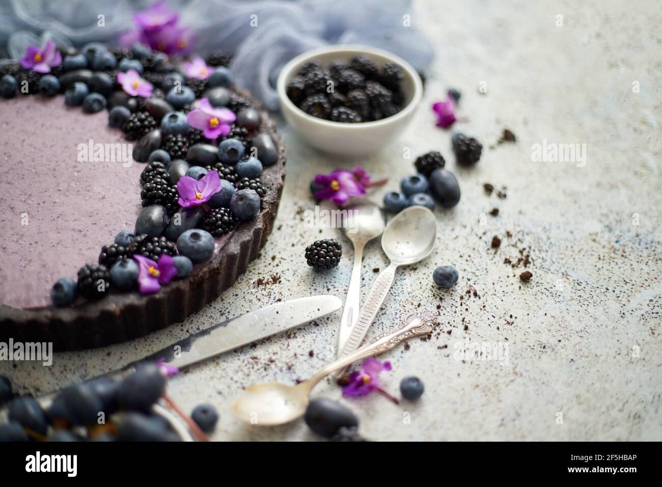 Tarta dulce y sabrosa con arándanos frescos, moras y uvas, servida sobre fondo de piedra Foto de stock