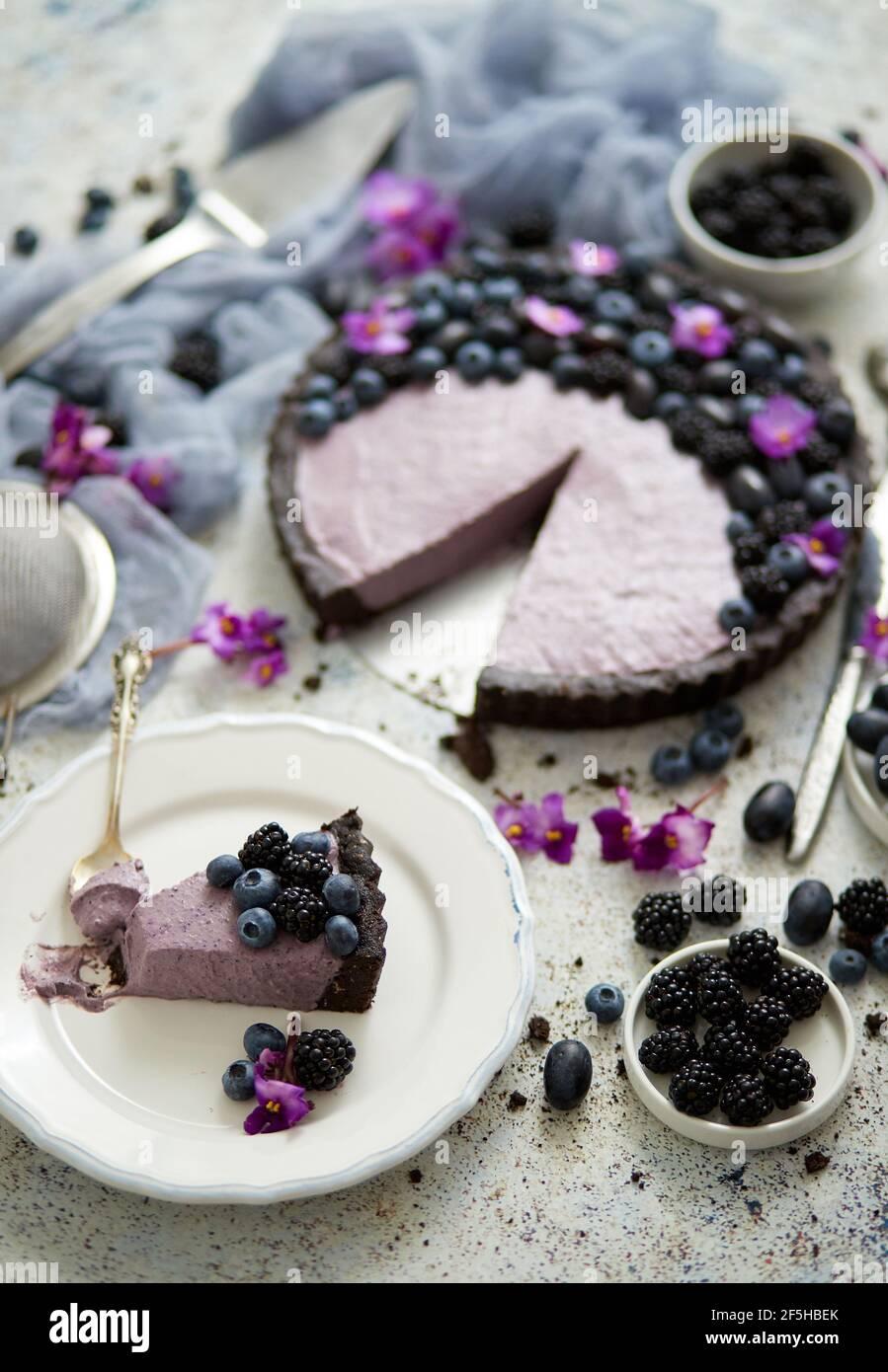 Plato con un pedazo casero de delicioso arándanos, mora y tarta de uva servida en la mesa Foto de stock