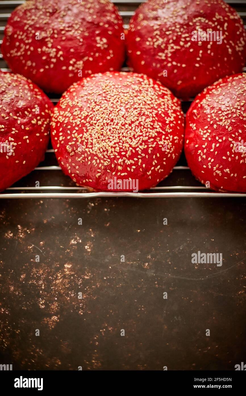 Panecillos de hamburguesa caseros de color rojo recién horneados con vista superior de sésamo. Se coloca en una parrilla de metal. Foto de stock