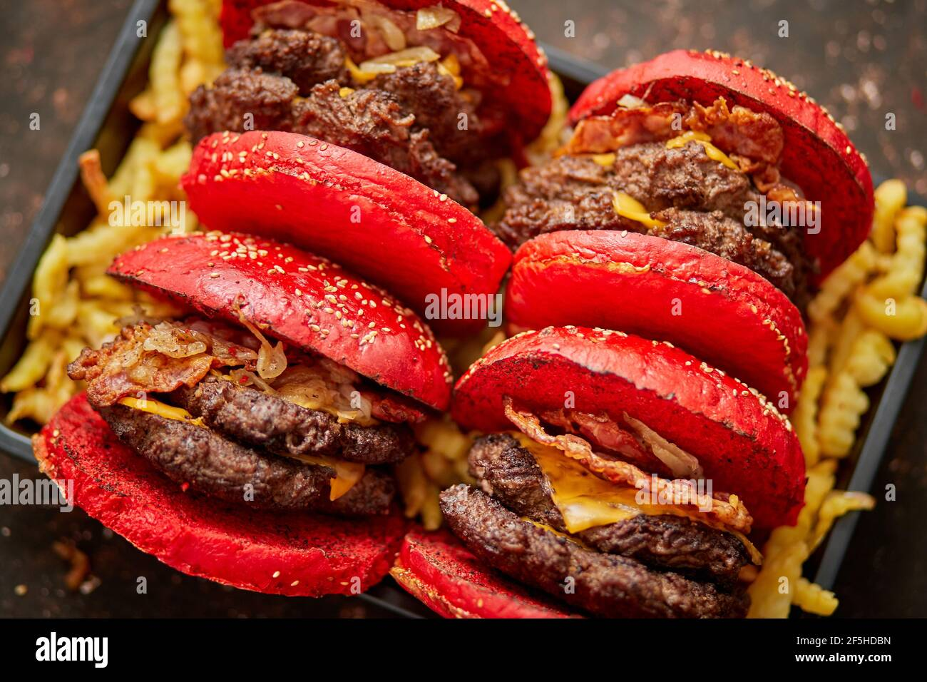 Juego de cuatro hamburguesas de queso de becon doble gigante caseras. Se sirve con patatas fritas a bordo de madera. Foto de stock