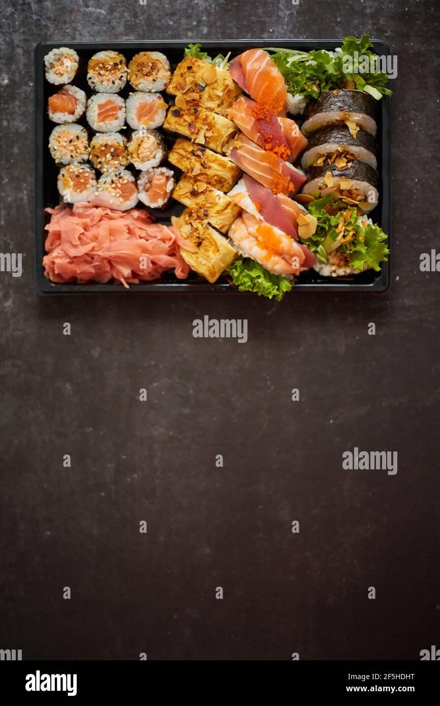 Sushi Bandeja de plástico para llevar con diferentes tipos de rollos y espacio de copia. Concepto de comida para llevar. Foto de stock
