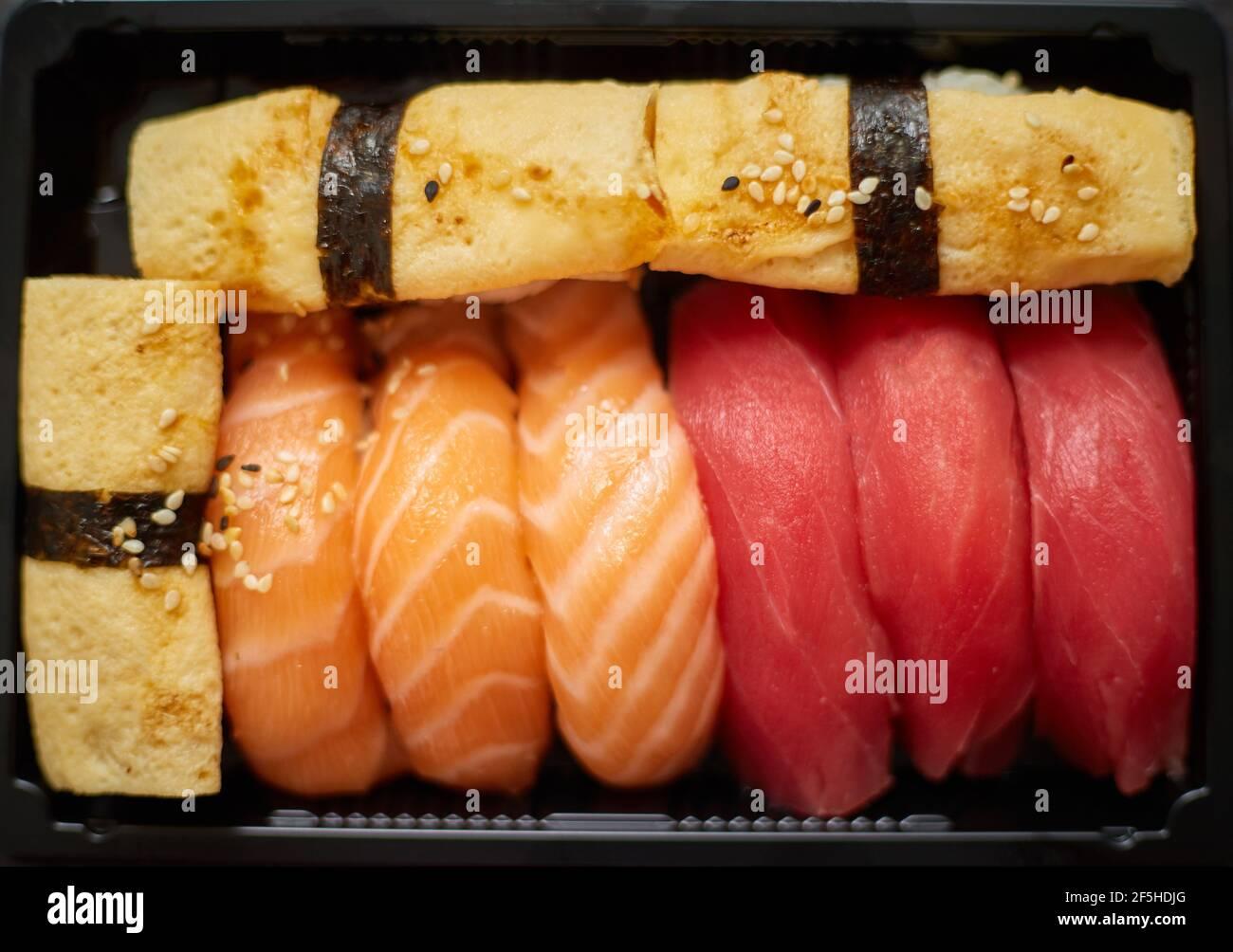 El sushi nigiri se prepara en un recipiente de plástico listo para la entrega para llevar. Cierre de la caja de comida para llevar Foto de stock