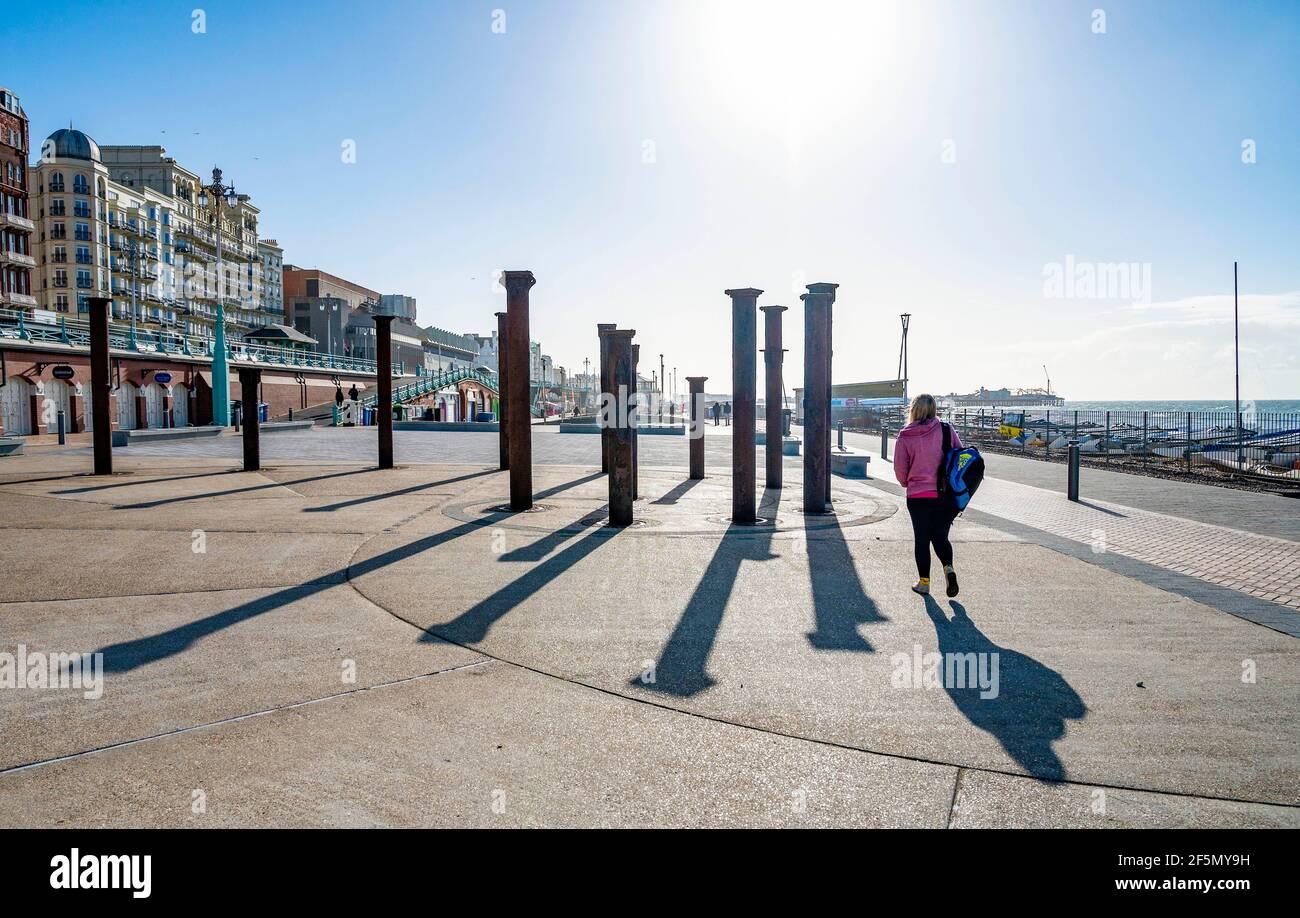 Brighton Reino Unido 27th Marzo 2021 - Caminantes Disfrute de una mañana soleada pero fría por la instalación de arte Golden Spiral en el paseo marítimo de Brighton. Se prevé que el clima se vuelva mucho más cálido la próxima semana, con temperaturas que se espera alcancen más de 20 grados en algunas partes del Reino Unido: Crédito Simon Dack / Alamy Live News Foto de stock