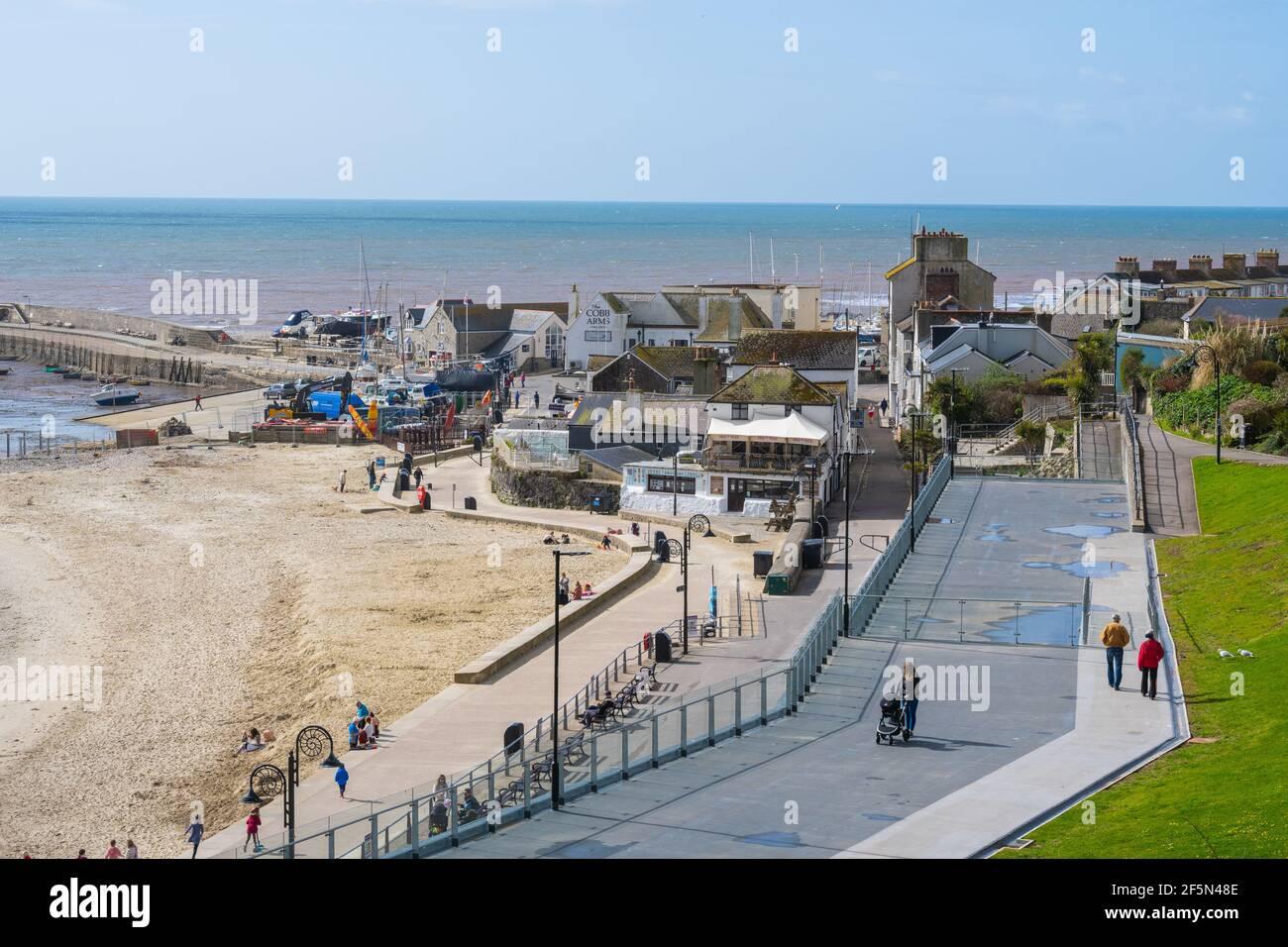 Lyme Regis, Dorset, Reino Unido. 27th de marzo de 2021. Tiempo en el Reino Unido: Después de un comienzo frío, había un montón de rachas de sol en la estación costera de Lyme Regis hoy. La gente de la zona estaba a punto de disfrutar del sol de primavera, pero la playa era tranquila para esta época del año. Se espera que la bonita ciudad costera esté más ocupada la próxima semana, ya que las restricciones de bloqueo de coronavirus finalmente comienzan a aliviarse. Crédito: Celia McMahon/Alamy Live News Foto de stock