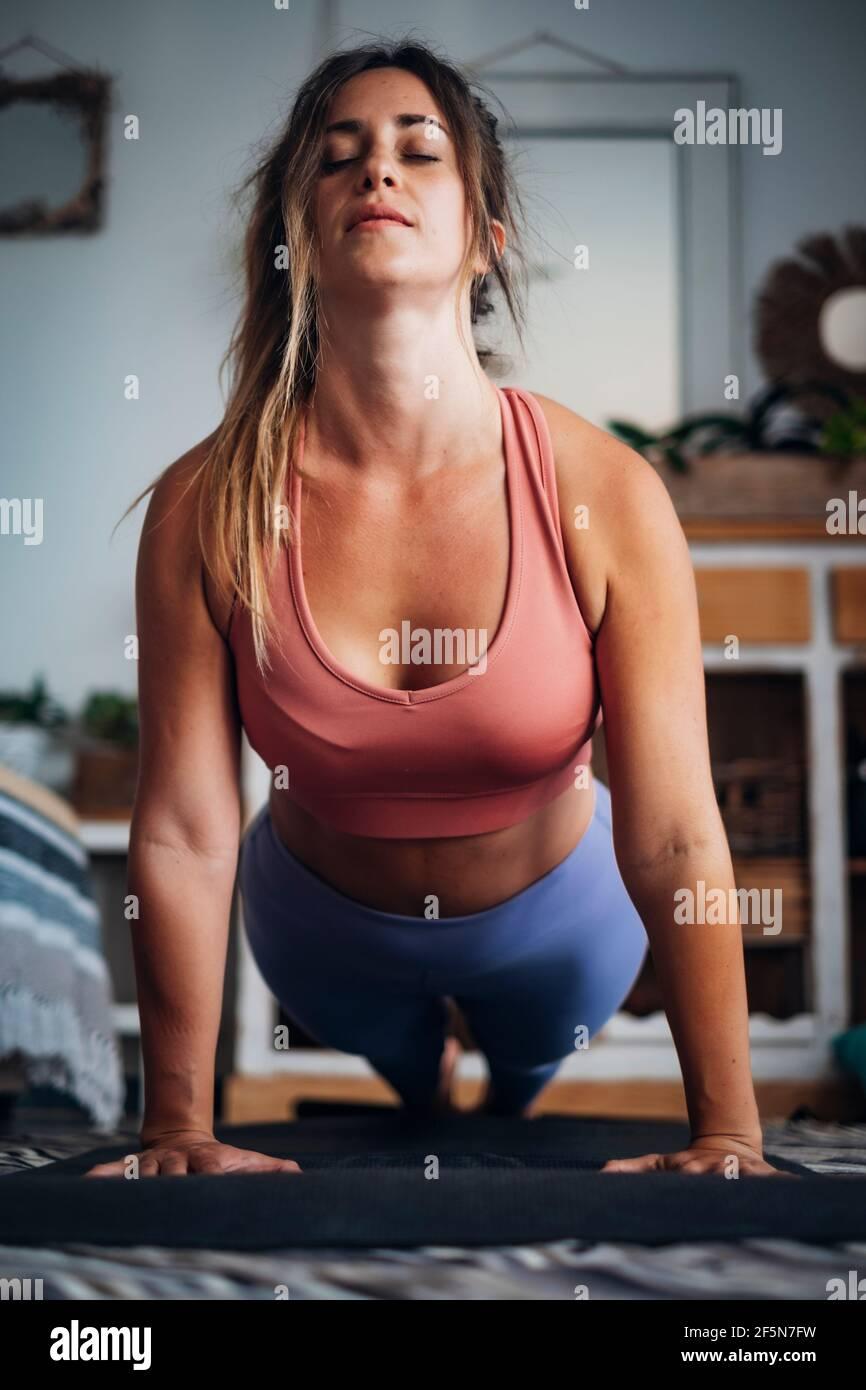 Hermoso deporte de chica en casa. Ejercicio físico, abs, entrenamiento inteligente, ejercicio, ejercicio en casa - empuje hacia arriba posición equilibrada para la gente de estilo de vida saludable Foto de stock