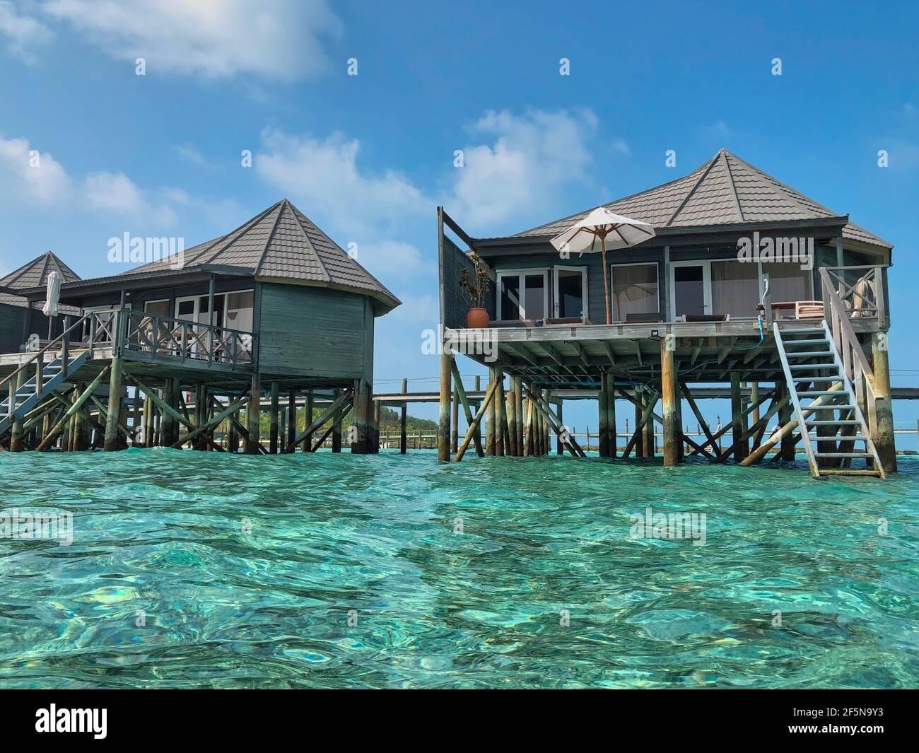Villa de agua de madera con Océano Turquoise en Maldivas. Hermosa vista de los bungalows sobre el agua con el mar de Lacadive en Maldivian Resort Komandoo. Foto de stock